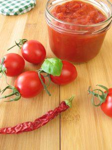 Frische Tomaten mit einem Glas Tomatenmark auf einem Holztisch